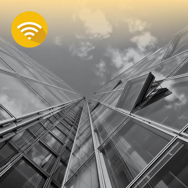 צילום של בנינים מלמטה על רקע השמיים ואייקון של שידורי טלוויזיה, רדיו וקבצי מדיה